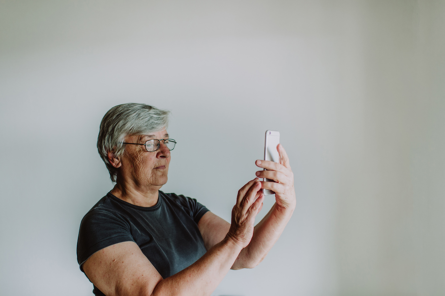 Old woman taking a selfie with mobile phone