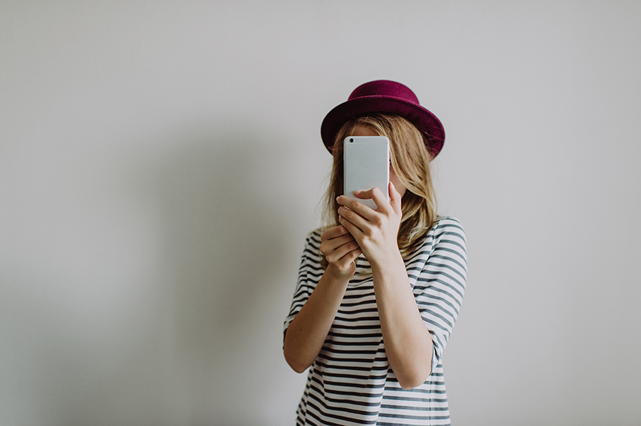 Girl taking picture on her phone in front of camera