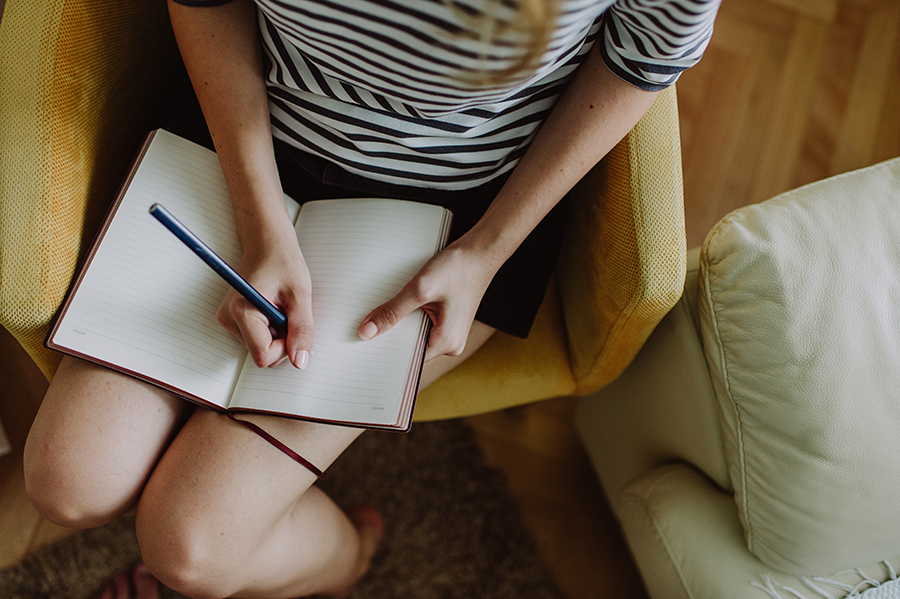 Girl sitting and writing in her notebook